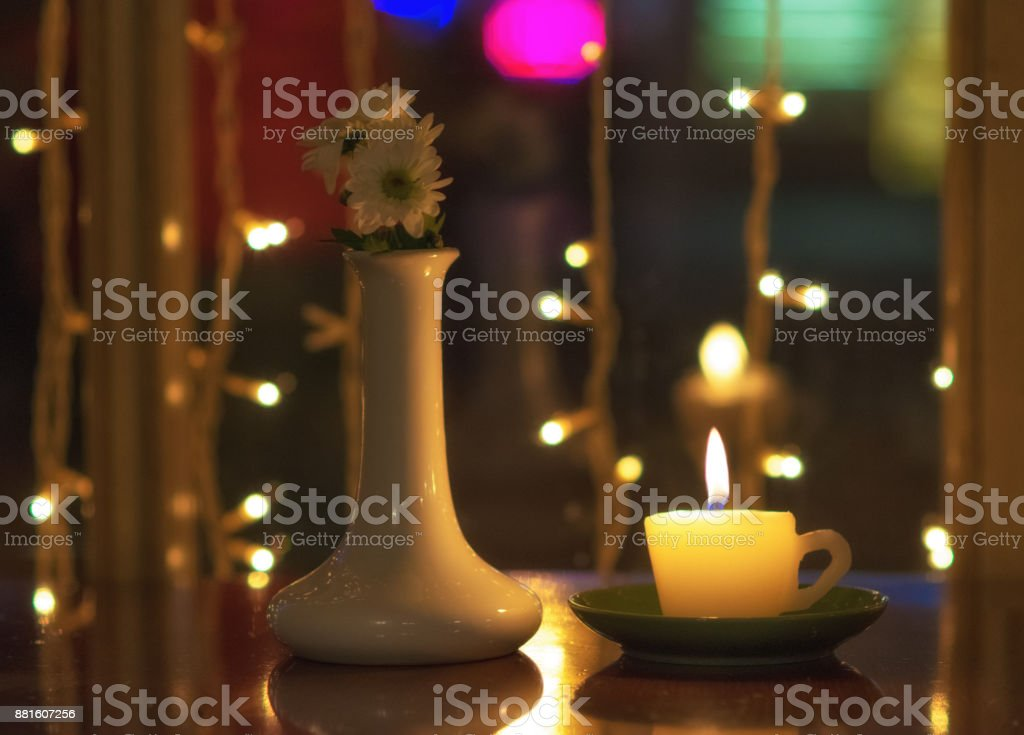 Burning Candle And White Vase With Flowers Inside On A Table In The