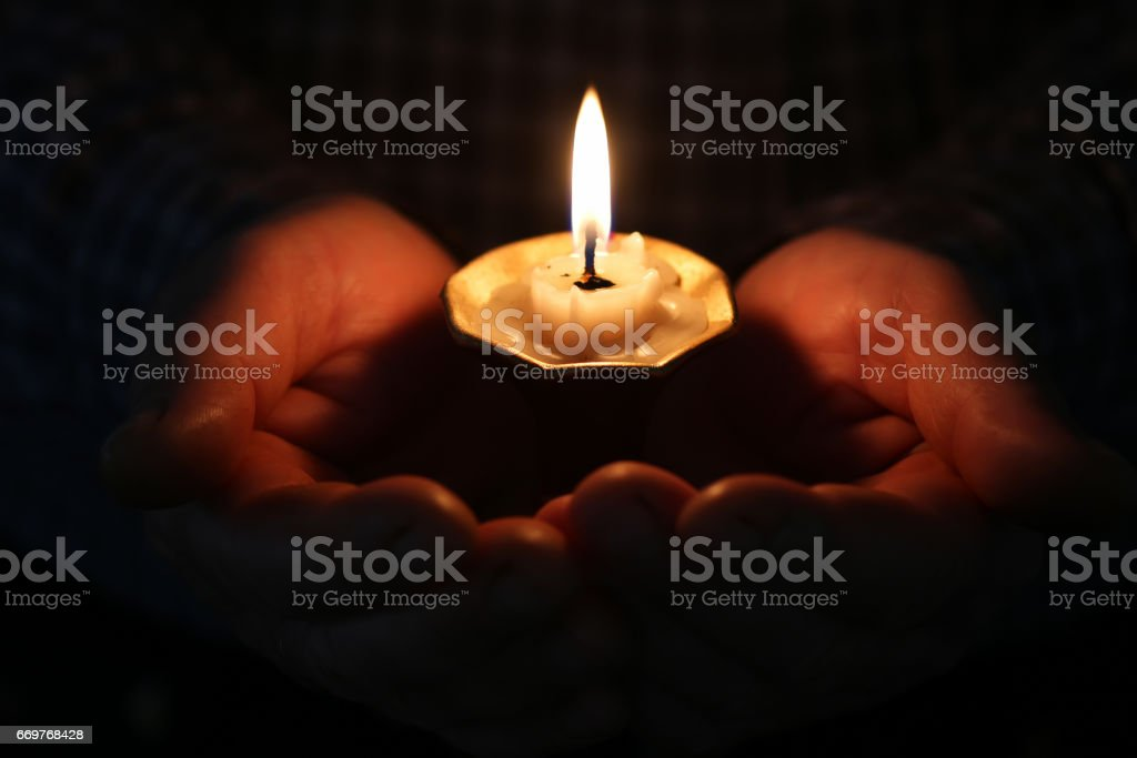 burning candle in a hand stock photo
