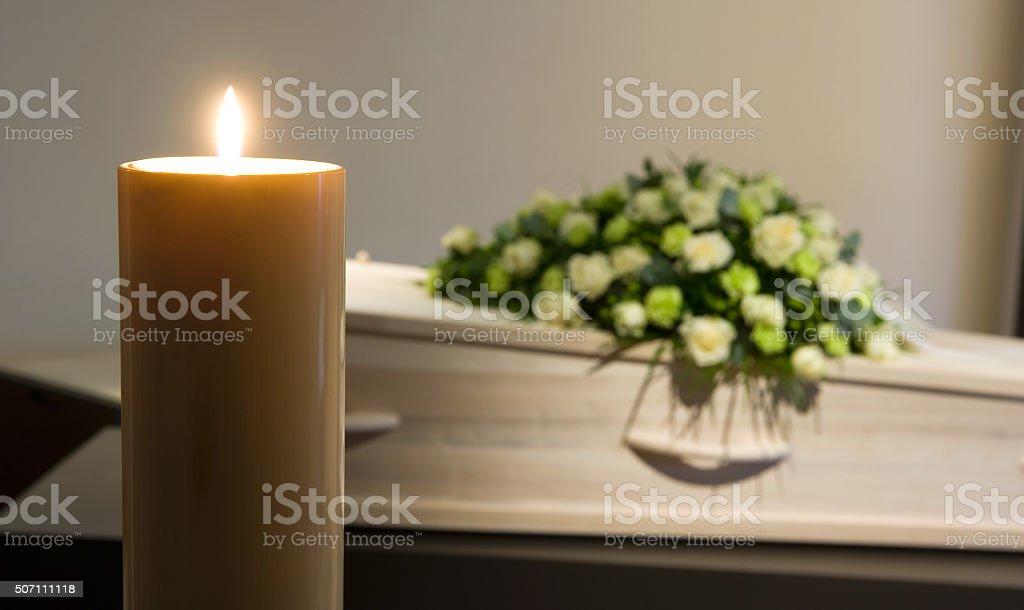 Burning candle in front of coffin stock photo