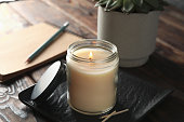 istock Burning candle in glass jar, succulent and notebook on wooden background, close up 1195997750