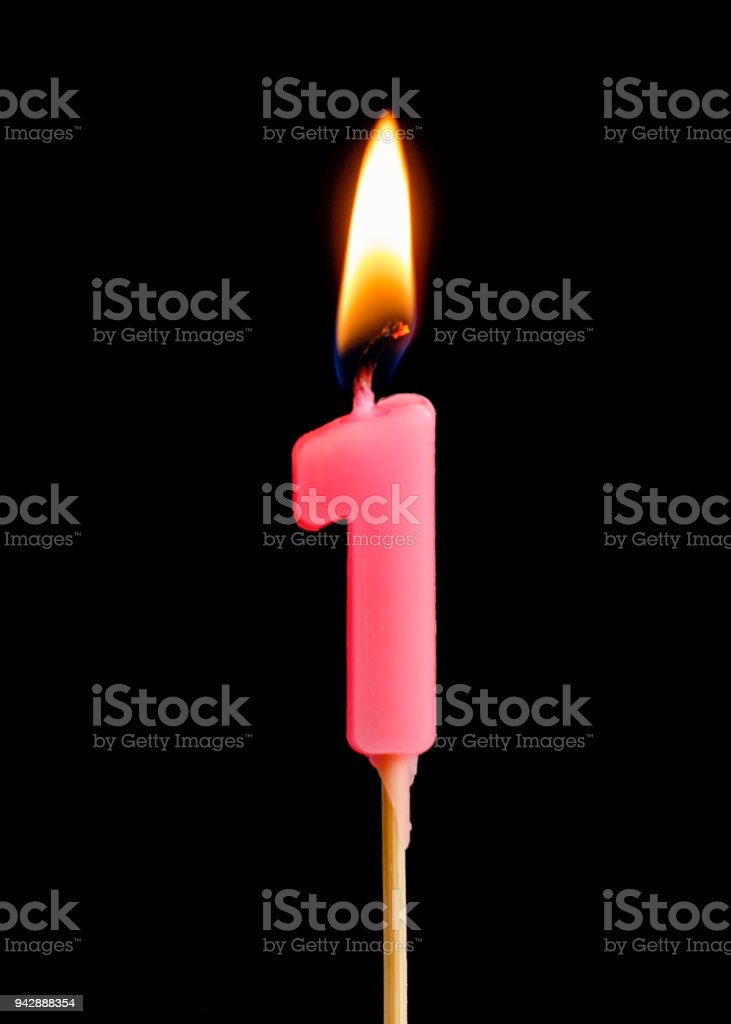 Burning candle in the form of one figures (numbers, dates) for cake isolated on black background. The concept of celebrating a birthday, anniversary, important date, holiday, table setting, cake decoration stock photo