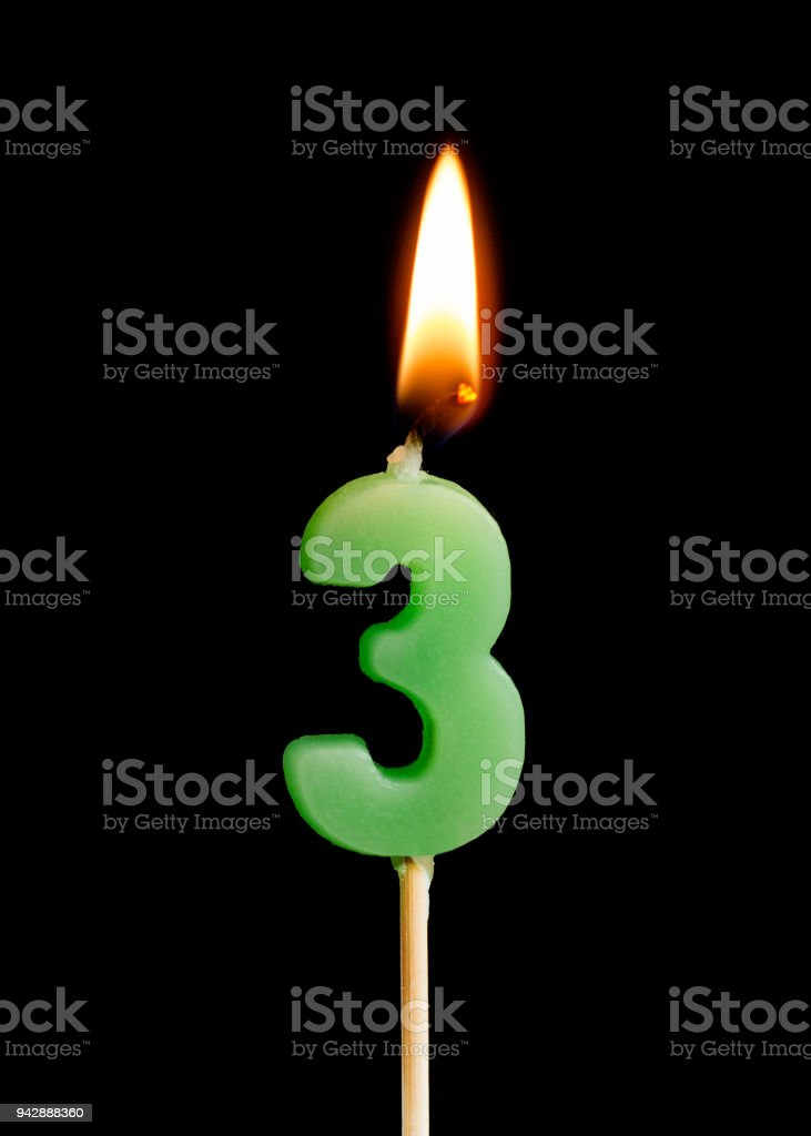 Burning candle in the form of three figures (numbers, dates) for cake isolated on black background. The concept of celebrating a birthday, anniversary, important date, holiday, table setting, cake decoration stock photo
