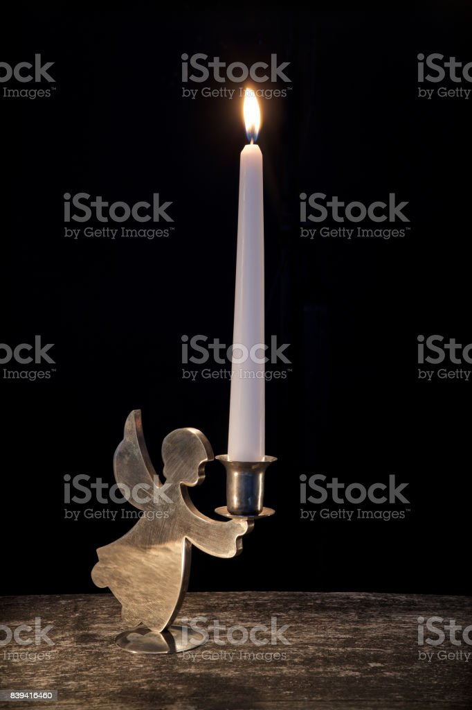 burning candle in vintage candlestick on black stock photo