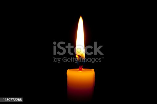 Burning candle isolated on black background. Copy space. Close up.