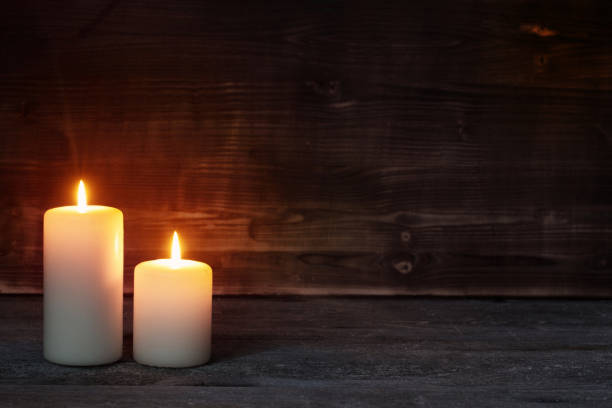 Burning candle on old wooden background stock photo