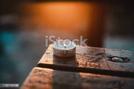 A burning candle on wooden table