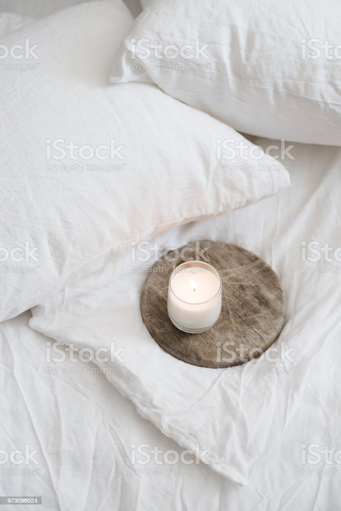 Burning candle on wooden tray on white natural linen stock photo