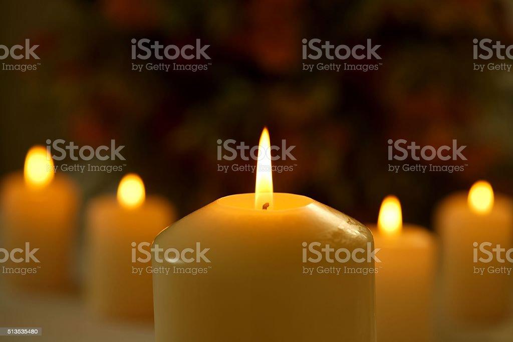 Burning candles against blurred flower background stock photo