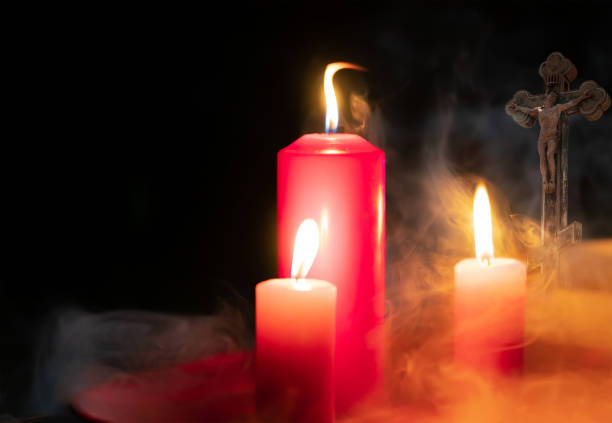 Burning candles and a crucifix on a black background.