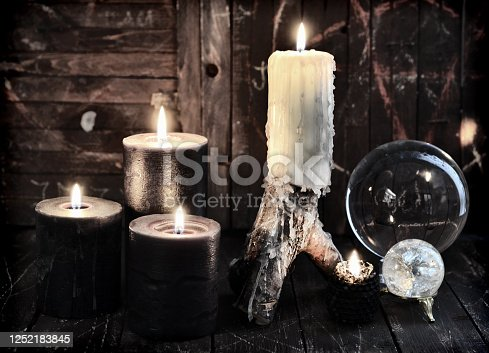 811119304 istock photo Burning candles and divination crystal ball on witch table 1252183845