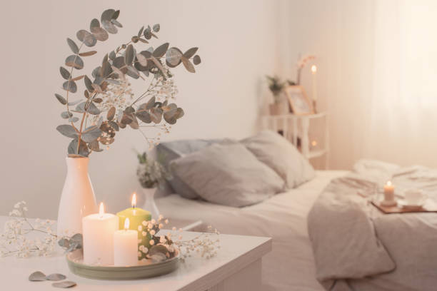 burning candles and eucalyptus in  vase in white bedroom stock photo