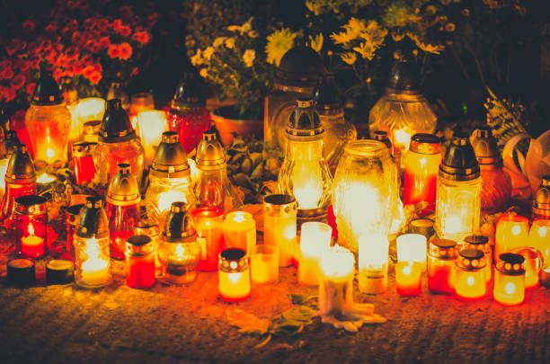 burning candles and lanterns in cemetery at night, funeral concept