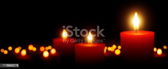 Burning candles gently glowing in the dark: tranquil low-key shot with shallow depth of field; for Christmas, spiritual and many more uses