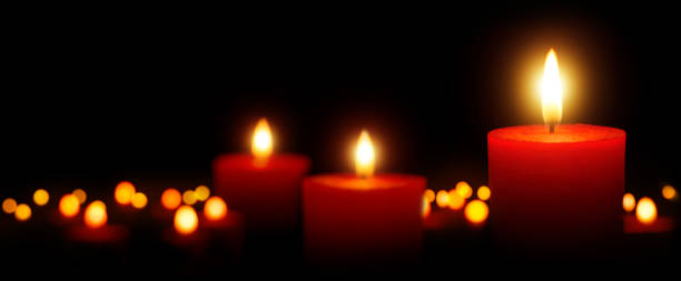 Burning candles gently glowing in the dark stock photo