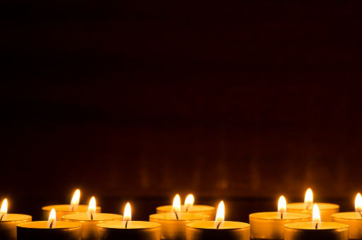 closeup to burning candles in darkness