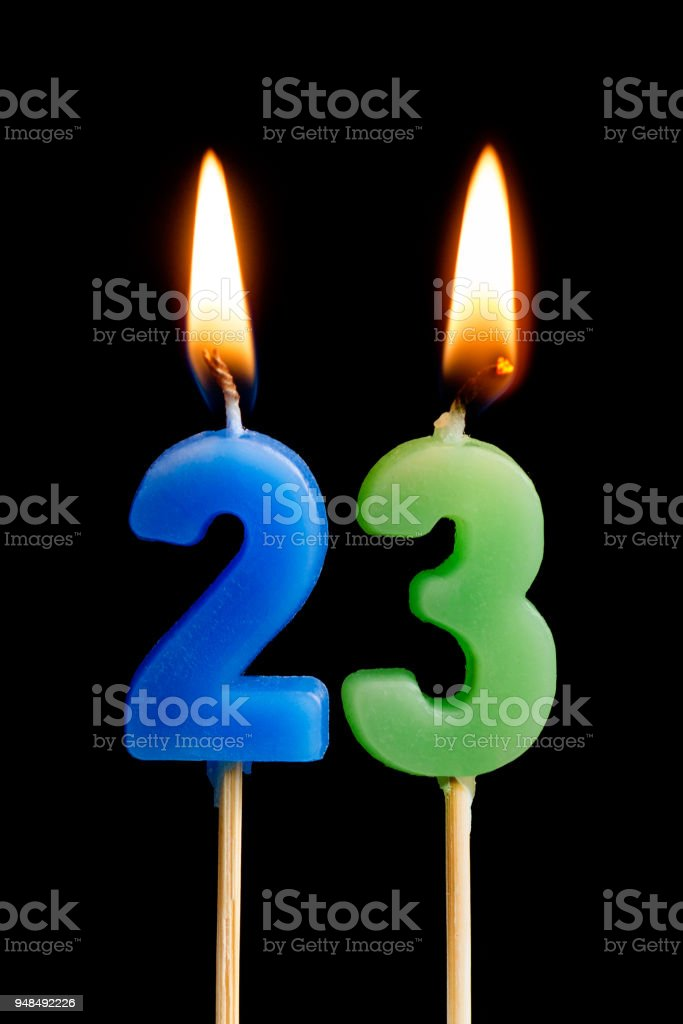 Burning candles in the form of 23 twenty three (numbers, dates) for cake isolated on black background. The concept of celebrating a birthday, anniversary, important date, holiday, table setting stock photo