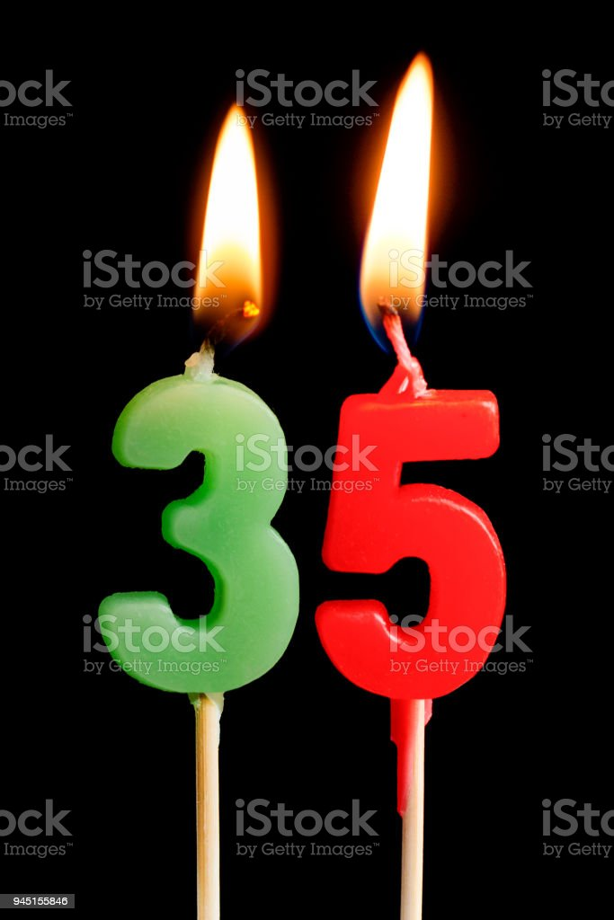 Burning candles in the form of 35 thirty five figures (numbers, dates) for cake isolated on black background. The concept of celebrating a birthday, anniversary, important date, holiday, table setting stock photo
