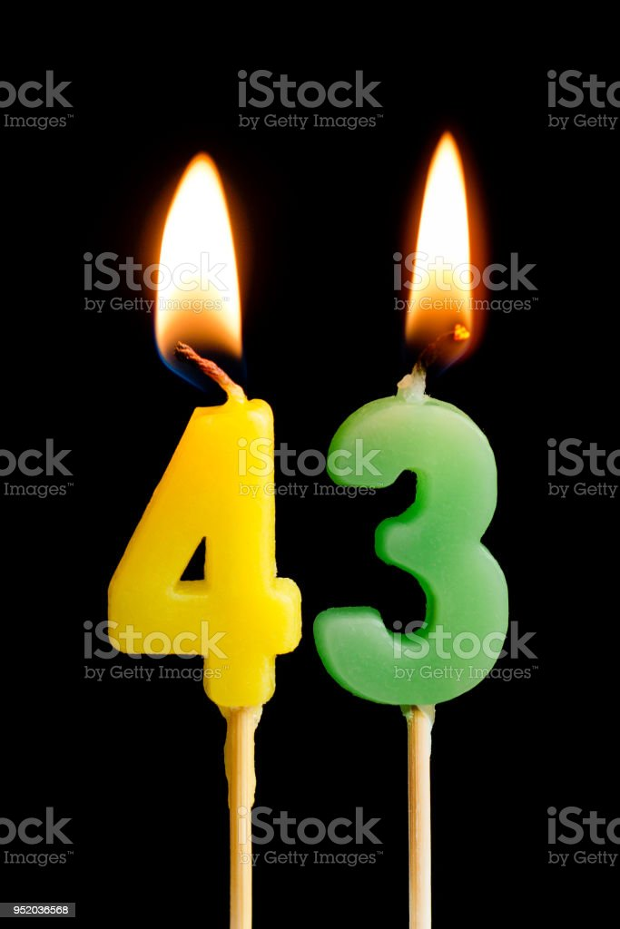Burning candles in the form of 43 forty three (numbers, dates) for cake isolated on black background. The concept of celebrating a birthday, anniversary, important date, holiday, table setting stock photo
