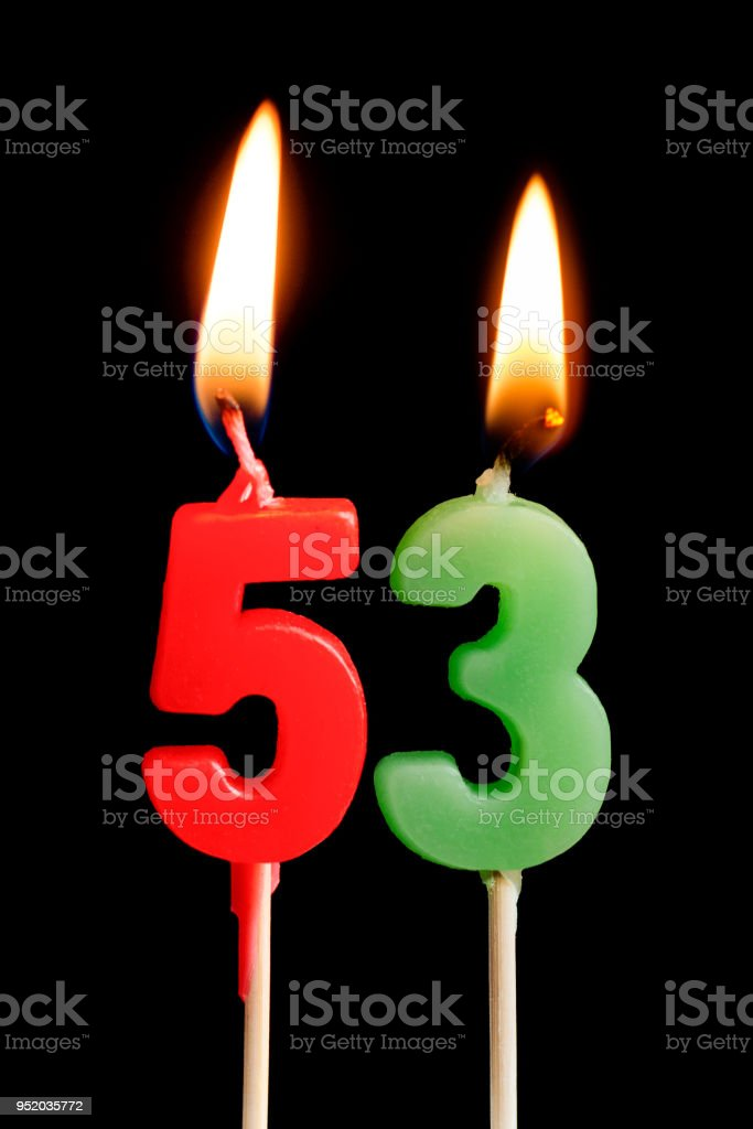 Burning candles in the form of 53 fifty three (numbers, dates) for cake isolated on black background. The concept of celebrating a birthday, anniversary, important date, holiday, table setting stock photo
