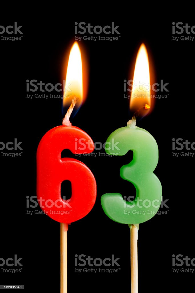 Burning candles in the form of 63 sixty three (numbers, dates) for cake isolated on black background. The concept of celebrating a birthday, anniversary, important date, holiday, table setting stock photo