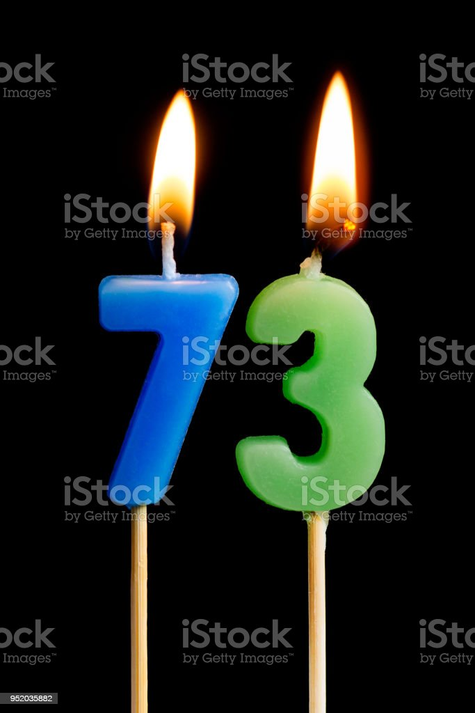 Burning candles in the form of 73 seventy three (numbers, dates) for cake isolated on black background. The concept of celebrating a birthday, anniversary, important date, holiday, table setting stock photo