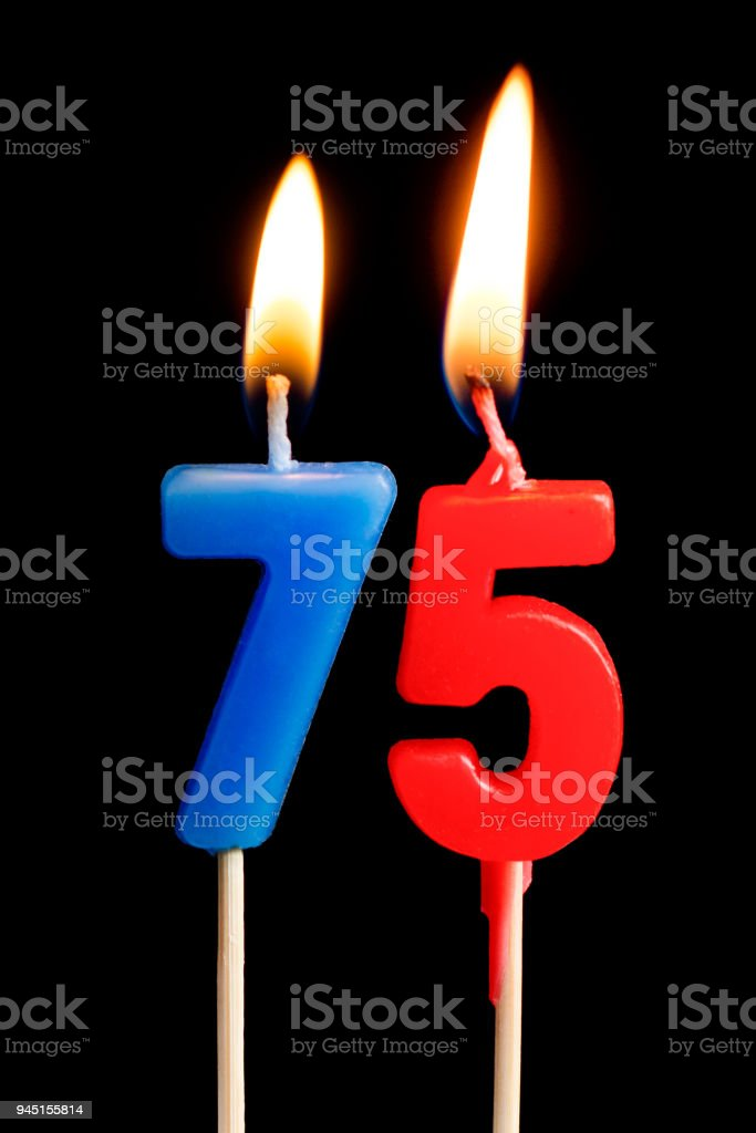 Burning candles in the form of 75 seventy five figures (numbers, dates) for cake isolated on black background. The concept of celebrating a birthday, anniversary, important date, holiday, table setting stock photo
