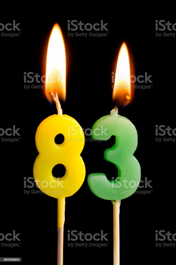Burning candles in the form of 83 eighty three (numbers, dates) for cake isolated on black background. The concept of celebrating a birthday, anniversary, important date, holiday, table setting stock photo