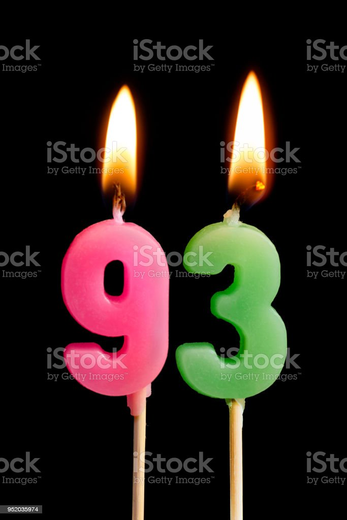 Burning candles in the form of 93 ninety three (numbers, dates) for cake isolated on black background. The concept of celebrating a birthday, anniversary, important date, holiday, table setting stock photo