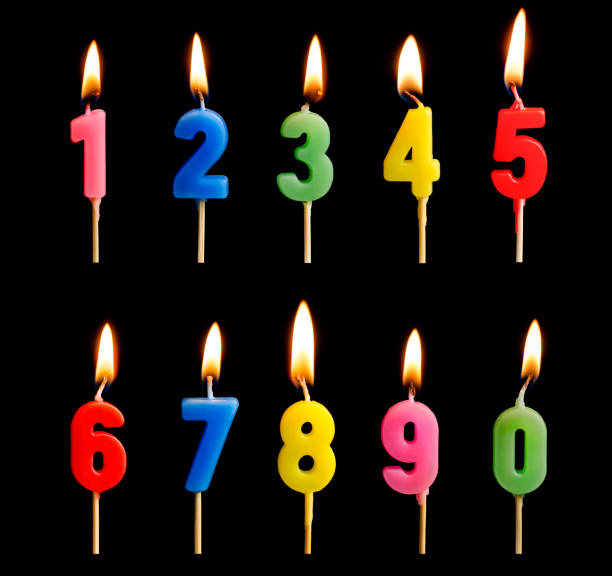 burning candles in the form of figures (numbers, dates) for cake isolated on black background. the concept of celebrating a birthday, anniversary, important date, holiday, table setting - число стоковые фото и изображения