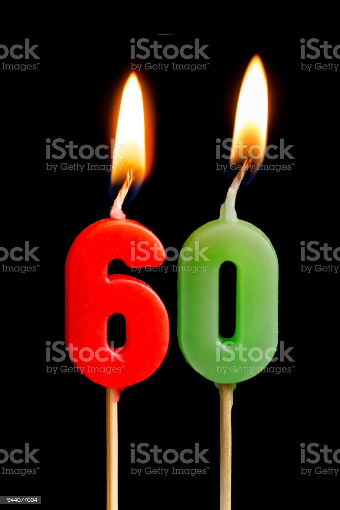 Burning candles in the form of sixty figures (numbers, dates) for cake isolated on black background. The concept of celebrating a birthday, anniversary, important date, holiday, table setting stock photo
