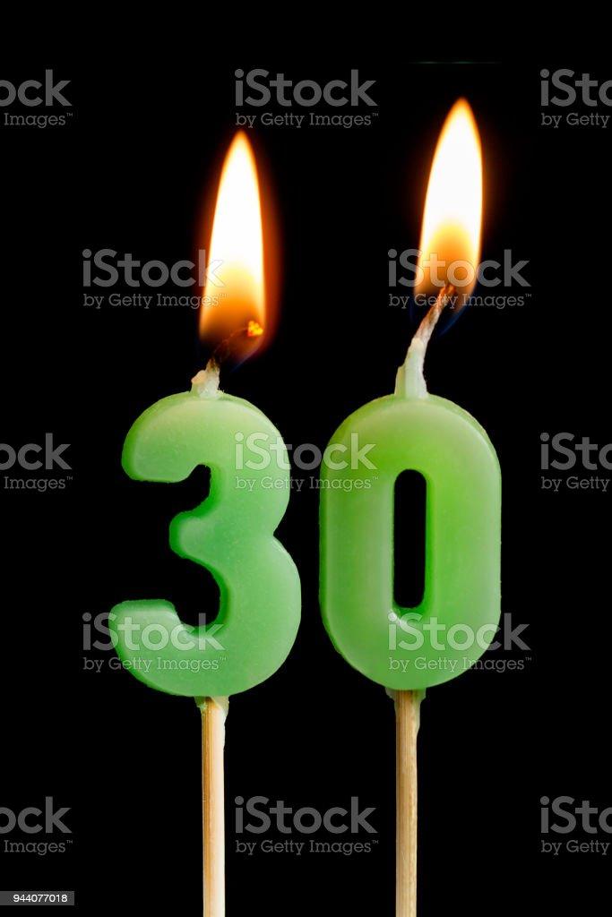 Quema de velas en forma de treinta figuras (números, fechas) para torta aislado sobre fondo negro. El concepto de la celebración de un cumpleaños, aniversario, fecha importante, vacaciones, tabla de ajuste - foto de stock
