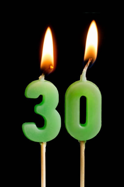 burning candles in the form of thirty figures (numbers, dates) for cake isolated on black background. the concept of celebrating a birthday, anniversary, important date, holiday, table setting - number 30 stock photos and pictures