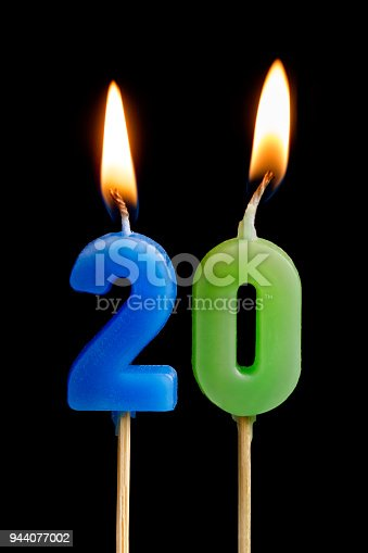 istock Burning candles in the form of twenty figures (numbers, dates) for cake isolated on black background. The concept of celebrating a birthday, anniversary, important date, holiday, table setting 944077002