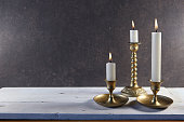Burning candles in retro candlesticks on white wooden table.