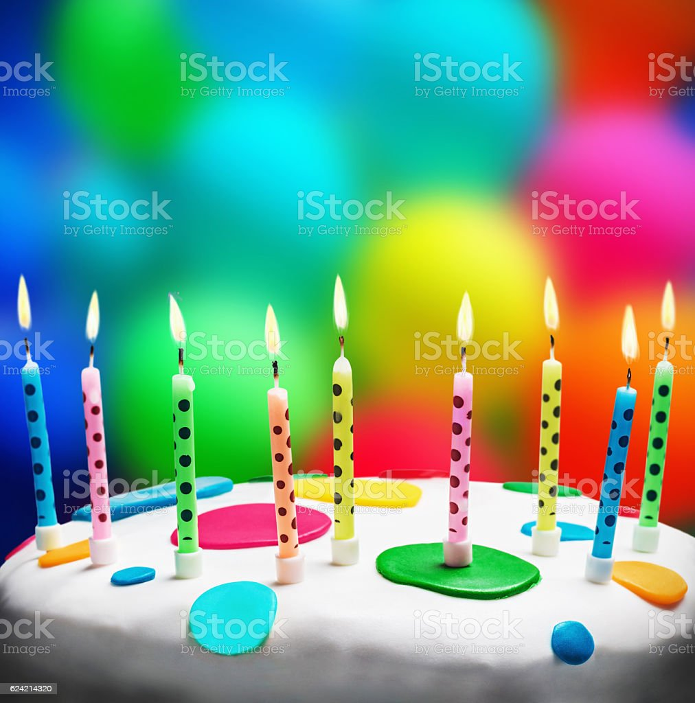 burning candles on a birthday cake stock photo