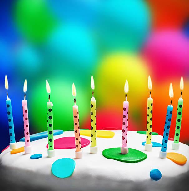 burning candles on a birthday cake stock photo
