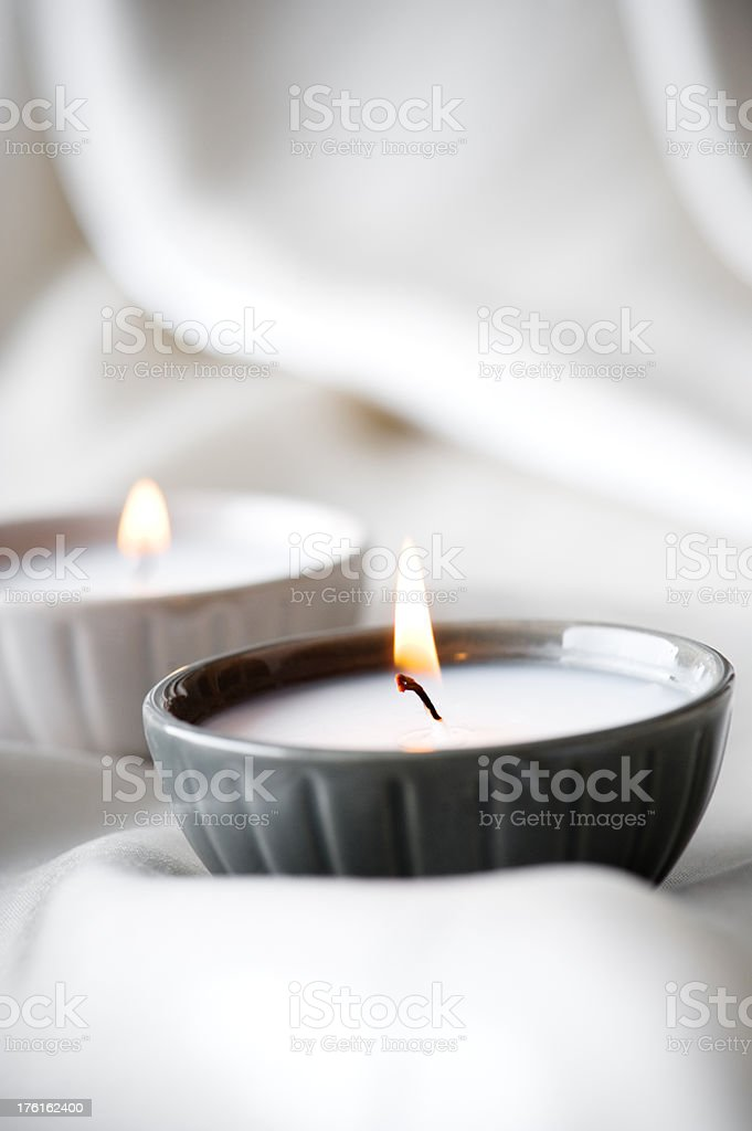 Burning candles on a satin background royalty-free stock photo