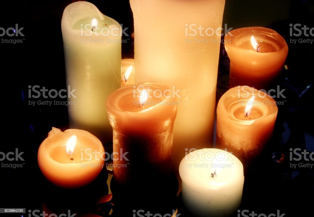 Burning candles on black background top view stock photo