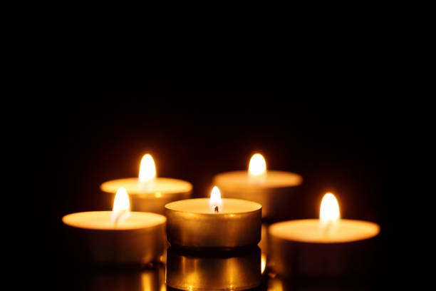 Burning candles on black Burning candles shot with shallow depth of field on black background mourning stock pictures, royalty-free photos & images