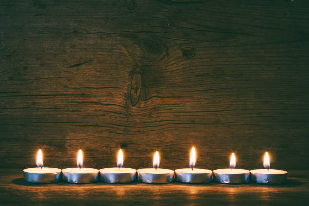 burning candles on the background of old barn boards, tinted photo stock photo