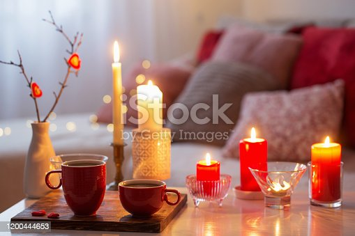 Burning candles on white table in interior. Valentines day concept