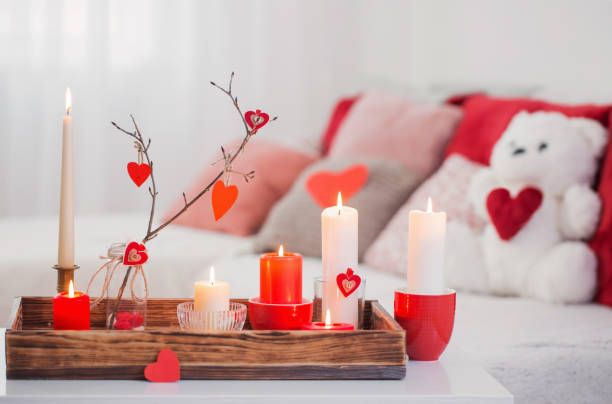 Burning candles on white table in interior. Valentines day conce stock photo