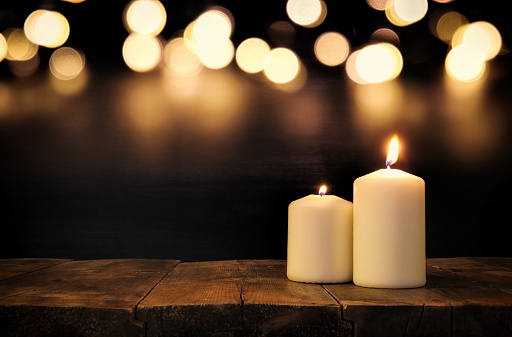 Burning candles over old wooden table with bokeh lights