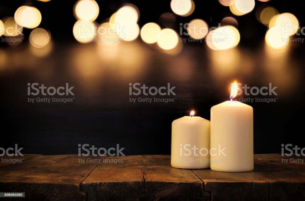 Burning candles over old wooden table with bokeh lights stock photo