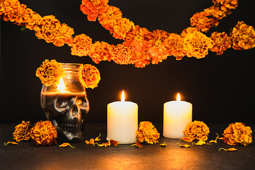 Burning candles, Skull with marigold flowers and garlands. Dia de los muertos day or day of the dead