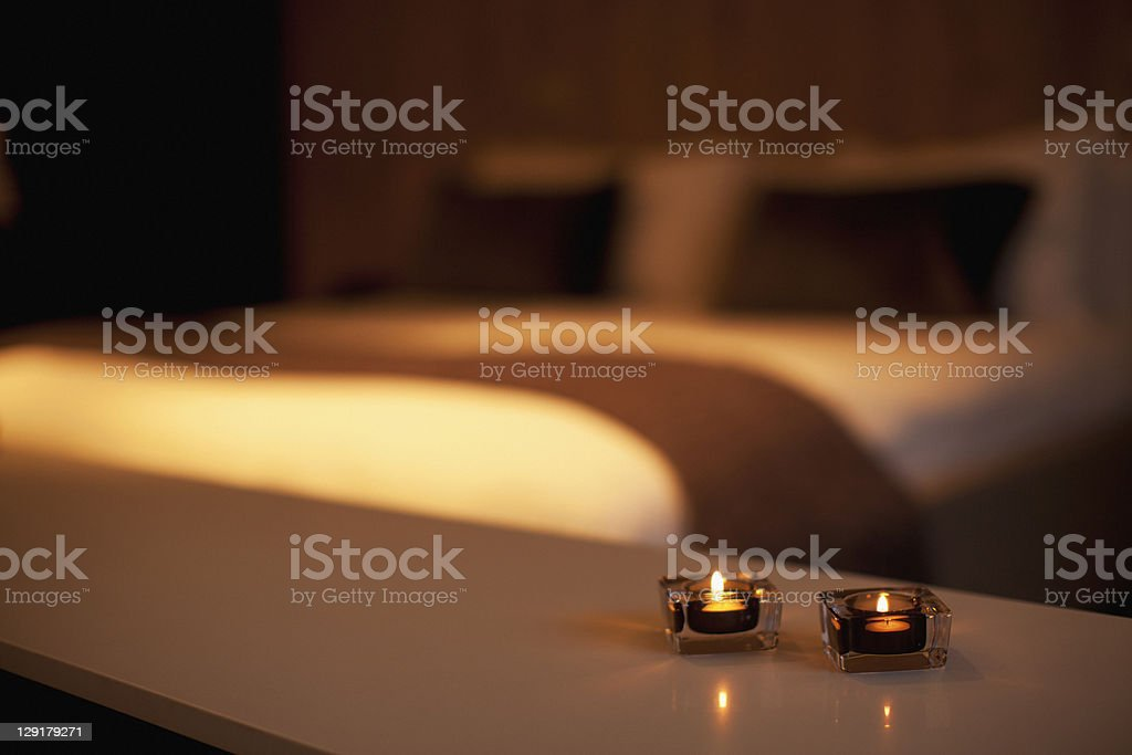 Burning candles with luxurious bed in the background royalty-free stock photo