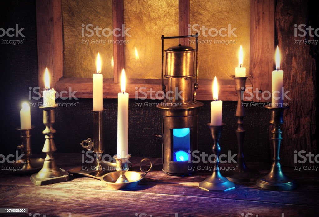 Burning candles,old candlestick and vintage ship lantern.Background with retro window frame.The holiday mood stock photo