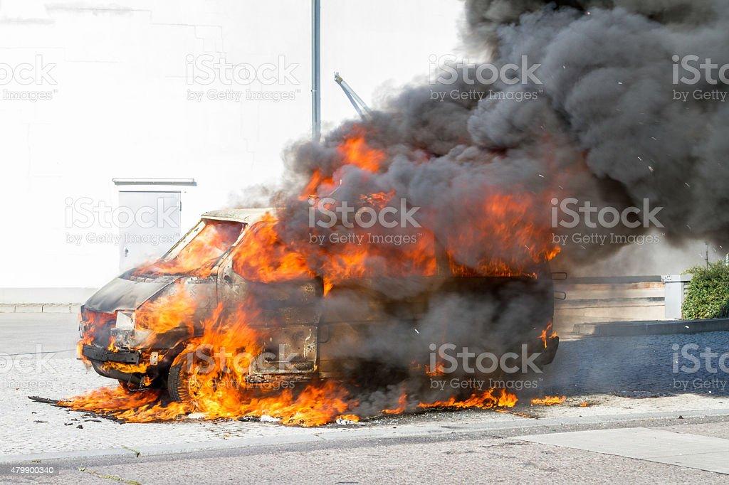 Burning car at Berlin near a supermarket. stock photo
