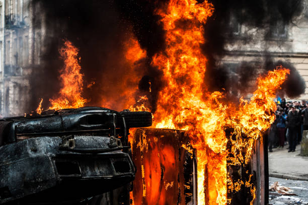 burning car. car destroyed and set on fire during the riots. city center car destroyed and set on fire during the riots. city center. clouds of smoke terrorism stock pictures, royalty-free photos & images