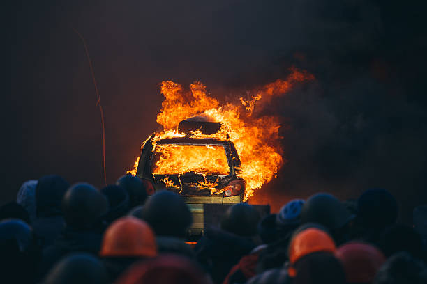 Burning car during anti-government riot Kiev, Ukraine - 18 February 2014: Protesters burns the car to restrain the riot police and make a lot of smoke for reduced visibility, because the police shoot at protesters. riot police stock pictures, royalty-free photos & images